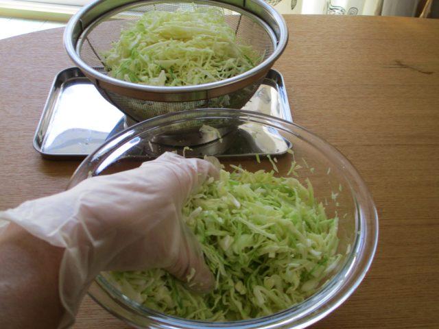 ボウルに半量のキャベツを入れ、その上に塩(小さじ1)を振り入れる。手袋をつけた手で、1分ほどよくもみ込みます。