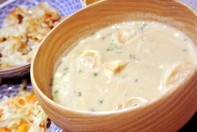 豆腐と白味噌・麦味噌をメインに作られた「はじまりの白」に、ネギとお麩のトッピング。写真は、炊き込み御飯(または玄米ご飯)、ガーリックが効いたペペロンチーノ風切り干し大根、蕗味噌がセットになった「一汁一菜セット」です。