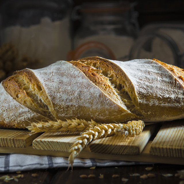 Pan de masa madre natural hecho a mano por un panadero tradicional decorado con espigas de trigo y centeno