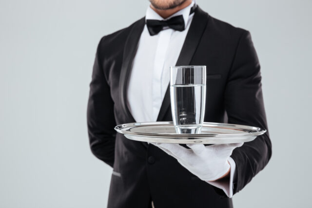 Closeup of butler in tuxedo and gloves holding silver tray with glass of water:Quick and Easy Hacco Recipes, as Enjoyed by Top Models