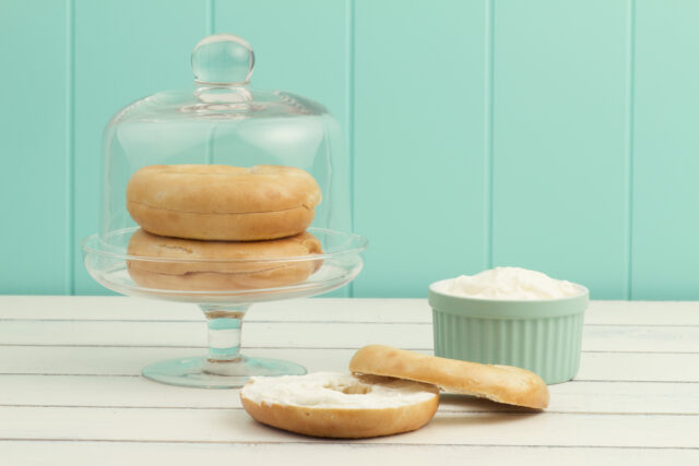 A bagel spread with cheese cream on a white wooden table. A turquoise bowl with cheese cream and two bagels in a cake stand with a cloche.