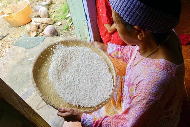 タペクタン作りの前日、イブが外に向かってタペクタン用のもち米のゴミや悪い米をより分ける