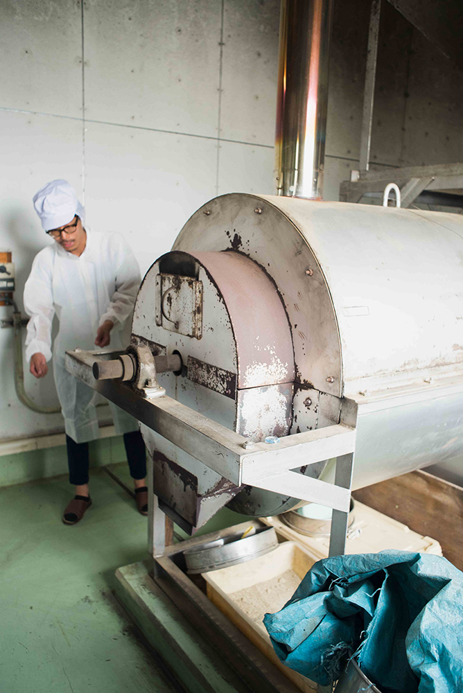 小麦を炒る機械の説明をしてくださる浄慶拓志さん